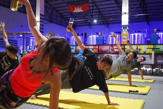 People participate in a beer yoga session, as the country eases the coronavirus disease (COVID-19) restrictions, at a craft brewery in Phnom Penh, Cambodia. REUTERS/Cindy Liu