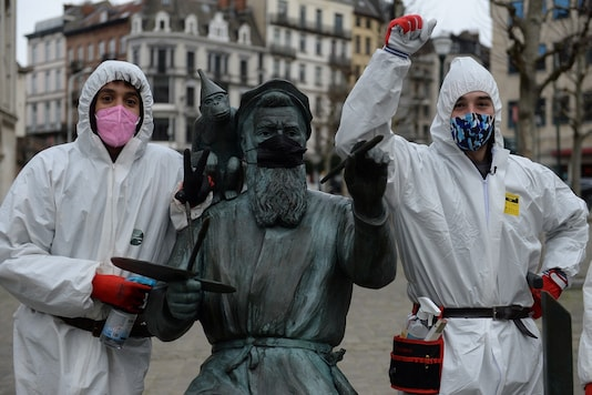 """A pair of recently-unemployed men, calling themselves the """"COVID boys"""", patrols in central Brussels to give advice about social distancing and mask wearing in , Belgium. REUTERS/Johanna Geron"""