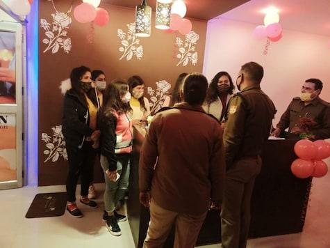 Officials of Dehradun police question staff of a  spa centre during a raid.
