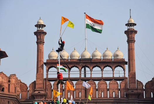 Farmers hoist flags at the Red Fort during the tractor rally on Republic Day. (Image: PTI)