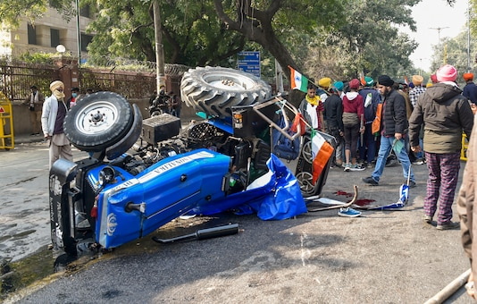 Farmers stand next to the overturned tractor at ITO. (Image: PTI)