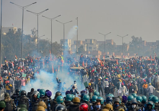 Police uses tear gas to disperse protesting farmers who were attempting to break barricades at Ghazipur border. (Image: PTI)