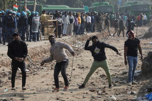 People shouting anti-farmers slogans throw stones, at a protest site at Singhu border near New Delhi on Friday. (Reuters)