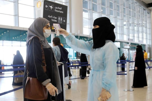A security woman checks the temperature of a woman at Riyadh International Airport.