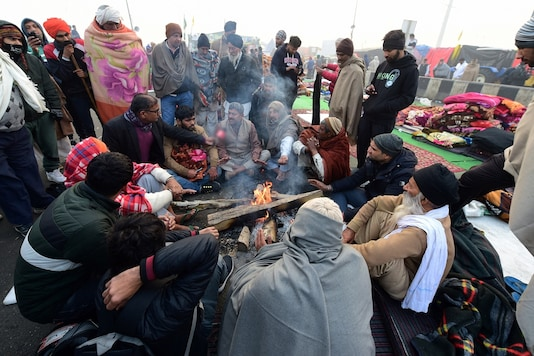 People sit around a bonfire to warm themselves on a cold morning in New Delhi, Friday. (Image: PTI)