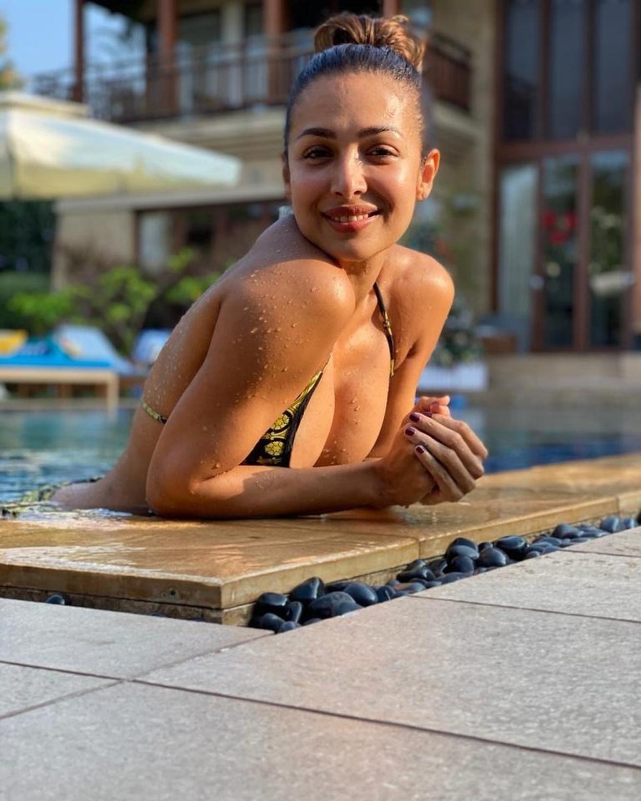 Malaika Arora flaunts her cleavage as she smiles for the camera while chilling in the pool. (Credit: Instagram)