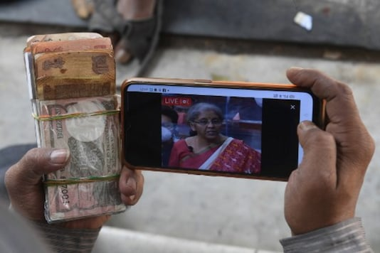 A man watches a live streaming of the Budget on his mobile phone, in Kolkata on Monday. (AFP)