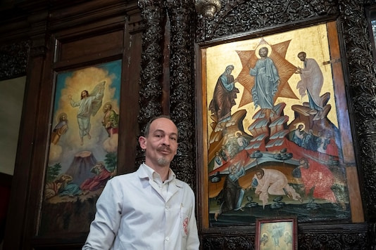 Venizelos Gavrilakis, a senior restorer and conservator from Thessaloniki, Greece, poses with the 16th century Byzantine Christian icon after completing its restoration at a Greek Orthodox church where he set up his laboratory in Istanbul, Turkey.  REUTERS/Murad Sezer