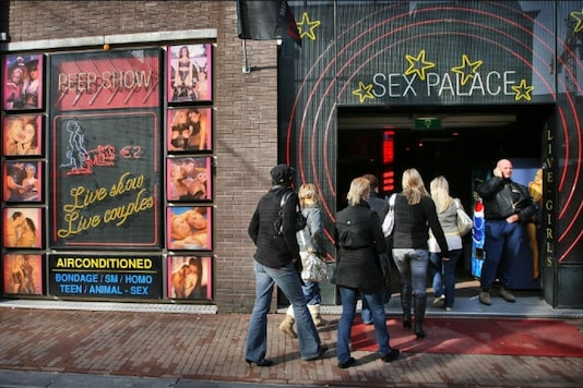 Visitors enter a peep-show theatre during the first-ever open day of Amsterdam's red light district February 18, 2006. REUTERS/Paul Vreeker/File Photo