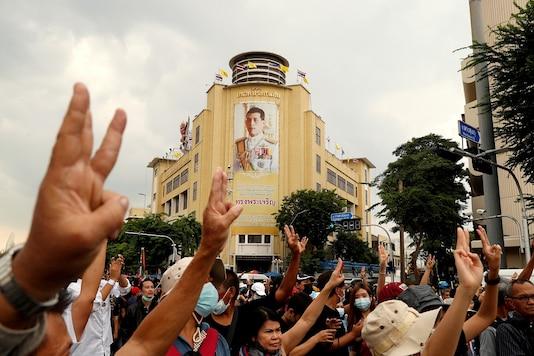 File photo:  A portrait of King Maha Vajiralongkorn is seen as pro-democracy demonstrators give a three-finger salute while marching during a Thai anti-government mass protest, on the 47th anniversary of the 1973 student uprising, in Bangkok, Thailand.  REUTERS/Jorge Silva/File Photo