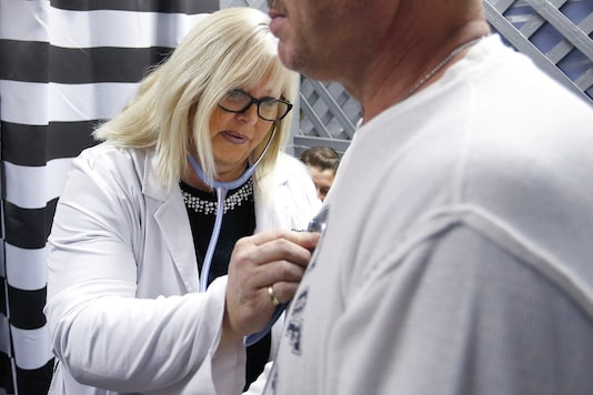 File photo of Dr Tricia Derges with a patient at the Lift Up Springfield medical clinic in Springfield.   (Nathan Papes/The Springfield News-Leader via AP)
