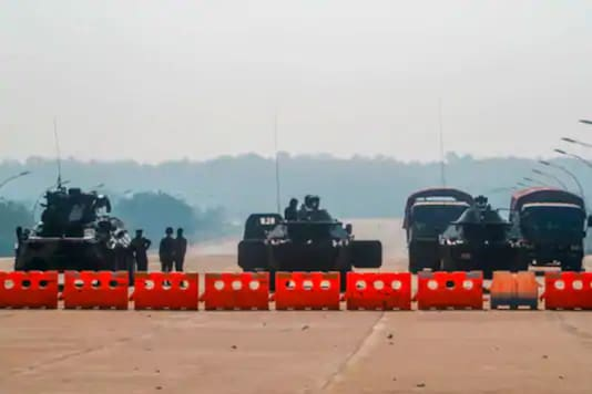 Myanmar's military personnel stand guard at a checkpoint manned with armored vehicles blocking a road leading to the parliament building Tuesday, Feb. 2, 2021, in Naypyitaw, Myanmar. (AP/PTI)