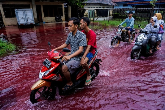 People ride motorbikes through a flooded road with red water due to the dye-waste from cloth factories, in Pekalongan, Central Java province, Indonesia.(Harviyan Perdana Putra/ via REUTERS)