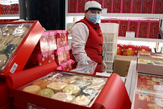A staff member stands behind Lunar New Year gift sets containing pastries at a food store, in Beijing.   (Credit: REUTERS/Florence Lo)