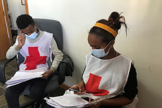Workers from the International Committee of the Red Cross (ICRC) check data before distributing relief supplies to civilians in Tigray region, Ethiopia January 4, 2021. (Credit: International Committee of the Red Cross/Handout via REUTERS)