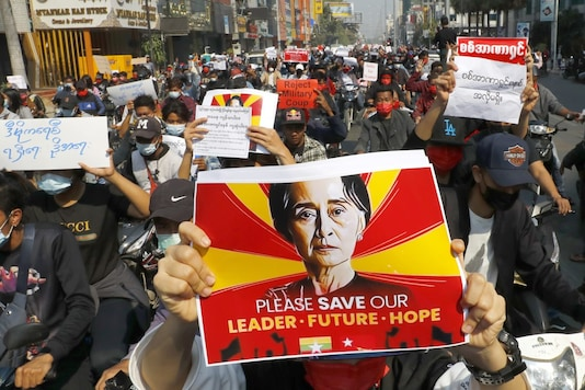 A protester holds an image of deposed Myanmar leader Aung San Suu Kyi as fellow protesters march around Mandalay, Myanmar on Monday, Feb. 8, 2021. A protest against Myanmar's one-week-old military government swelled rapidly Monday morning as opposition to the coup grew increasingly bold. (AP Photo)