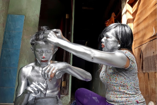 Puryanti, a 29-year-old woman, and her 15-year-old nephew Raffi, cover themselves from head to toe in silver paint to become 'manusia silver' (silver people), as part of their act to make a living. (Credit: REUTERS/Adi Kurniawan)
