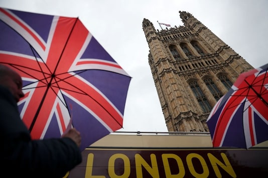 People carrying British Union Jack flag themed umbrellas walk past the Houses of Parliament in London, Britain. Reuters/File photo