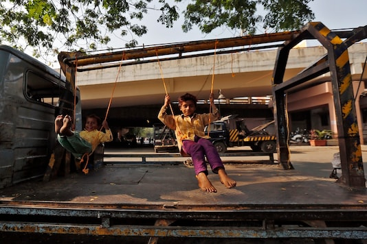 Children play on improvised swings on a tow truck parked on a roadside. (Image for representation/REUTERS)