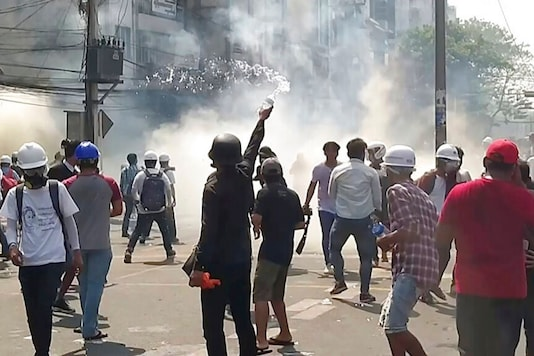In this image from a video, anti-coup protesters react as smoke from tear gas rises in Yangon, Myanmar on Sunday, February 28, 2021. (AP)