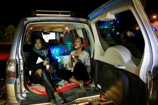 Women sit in a car as they watch a screening of the Sudanese European Film Festival at an outdoor, drive-through cinema. (Credit: EUTERS/Mohamed Nureldin Abdallah)
