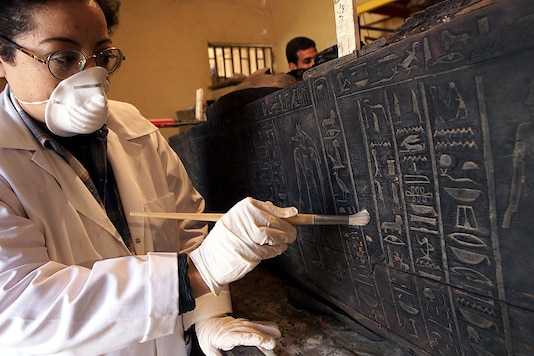 An Egyptian antiquities experts cleans a 3000-year-old sarcophagus. (Image for representation/ REUTERS)