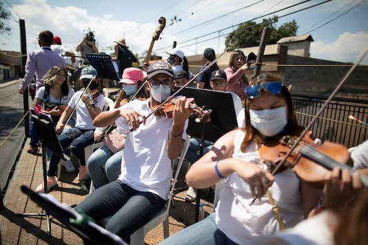 """Musicians join pianist, composer and conductor Jose Agustin Sanchez on the bed of an eighteen-wheeler truck for a musical tour called """"Musical Disinfection,"""" in Barquisimeto, Venezuela.  (AP Photo/Ariana Cubillos)"""