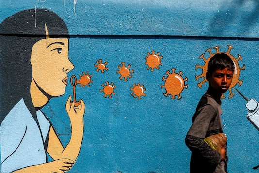 A boy walks past a graffiti amidst the spread of the coronavirus disease on a street in Navi Mumbai. (Image: Reuters)