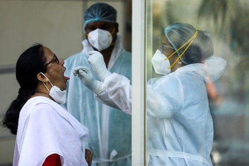 A healthcare worker in PPE collects a swab sample from a woman during a testing campaign for the coronavirus disease in Navi Mumbai. (Image: Reuters/File photo)