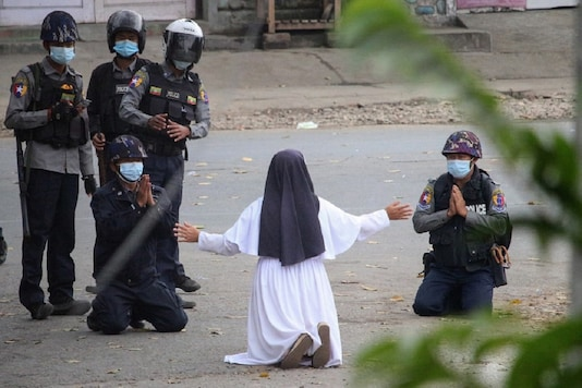 This handout photo taken on March 8 and released on March 9 by the Myitkyina News Journal shows a nun pleading with police not to harm protesters in Myitkyina in Myanmar's Kachin state, amid a crackdown on demonstrations against the military coup. (Photo by Handout / Myitkyina News Journal / AFP).