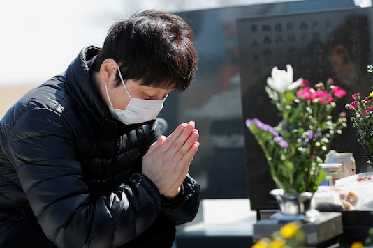 A person prays on the 10th anniversary of the 2011 earthquake and tsunami at a graveyard in Namie, Fukushima prefecture.  REUTERS/Kim Kyung-Hoon