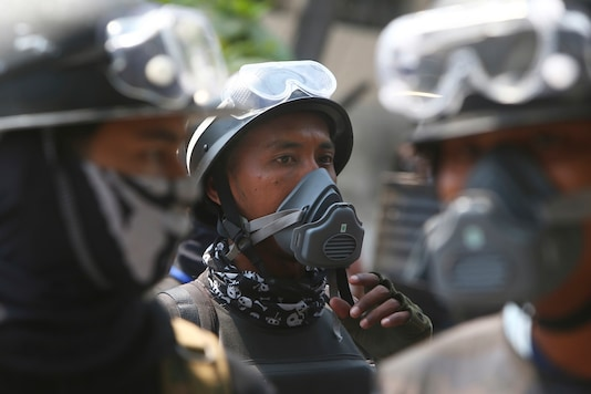 Protesters wear eye protection and face masks as they protest against the military coup in Mandalay, Myanmar, Friday. (AP Photo)