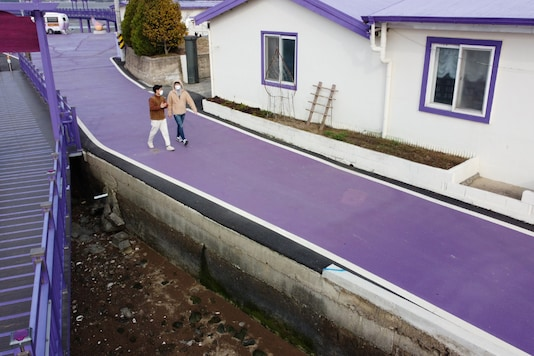 Tourists walk on a purple street at the Purple Island in Shinan, South Korea, March 9, 2021. Picture taken March 9, 2021. REUTERS/Daewoung Kim