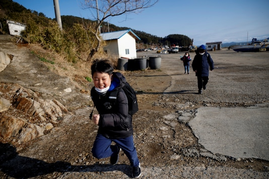 """Lyoo Chan-hee, 10, Lyoo Chae-hee, 7, and Kim Si-hu, 9, make their way to school on the first day of the new semester, on Nokdo island in Boryeong, South Korea, March 2, 2021. """"Seoul is so crowded, noisy and the air is not good,"""" said Chan-hee. """"Nokdo has no traffic, isn't noisy and the air is clean. I can play outside more actively, so I like it here."""" REUTERS/Kim Hong-Ji"""