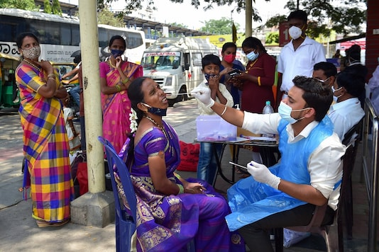A health worker conducts COVID-19 testing of a passenger at KSRTC bus stand, amid surge in coronavirus cases in Bengaluru, Wednesday (PTI)
