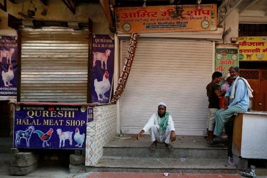 Representative image: People sit outside the closed meat shops in Gurugram, India, October 12, 2018. REUTERS/Adnan Abidi