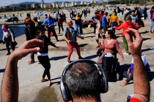 Barcelona residents use their headphones while listening to music as they dance during a socially-distant silent disco event on the first Spring weekend at Mar Bella beach in Barcelona, Spain March 21, 2021. REUTERS/Nacho Doce