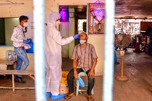 Mumbai: A heath worker, wearing PPE, conducts COVID-19 testing of a man at Dadar market, amid a surge in coronavirus cases across Maharashtra, in Mumbai, Monday, March 22, 2021. (PTI Photo)(PTI03_22_2021_000132B)