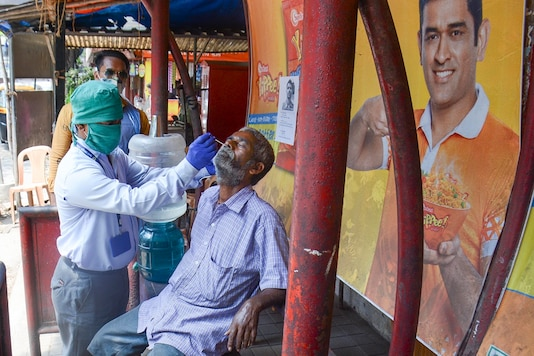 A medic takes swab sample from a person  for COVID-19 test amid surge in coronavirus cases, in Thane. (PTI Photo)