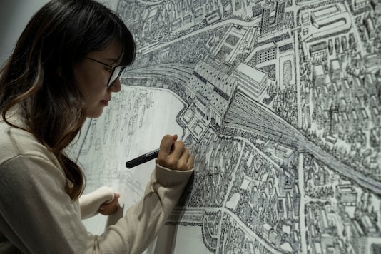 Chinese artist Yang Qian using dots to recreate an aerial view of Wuhan, China, under lockdown at her studio in Wuhan in central China's Hubei province on Sunday, Jan. 24, 2021. (AP Photo/Ng Han Guan)