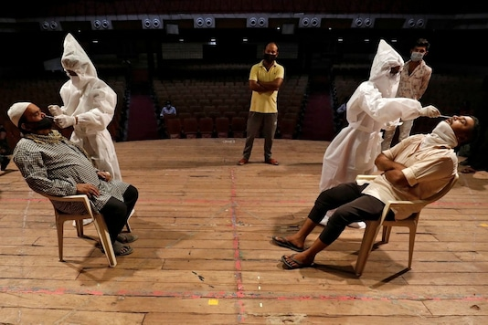 Healthcare workers wearing personal protective equipment (PPE) collect swab samples from men during a rapid antigen testing campaign for the coronavirus disease (COVID-19), at an auditorium turned into a testing centre in Ahmedabad. (REUTERS)