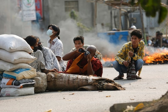 A Buddhist monk uses binoculars while with other men squatting behind a road barricade in Mandalay, Myanmar. (AP/PTI)
