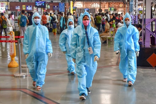 Health workers wearing PPE kits walk on a platform at CSMT, in Mumbai, Wednesday. (PTI)