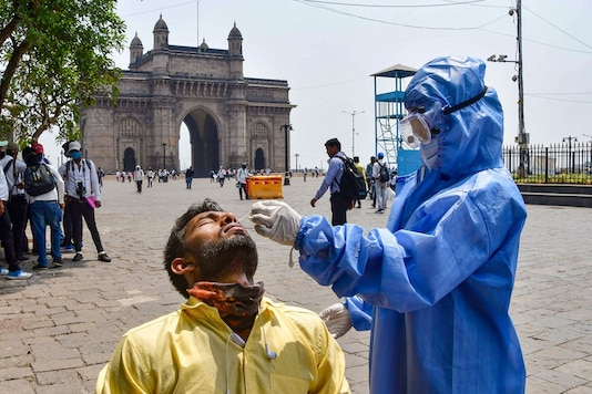 A health worker, wearing PPE kit, conducts COVID-19 test of a person at the Gateway of India in Mumbai. (PTI)
