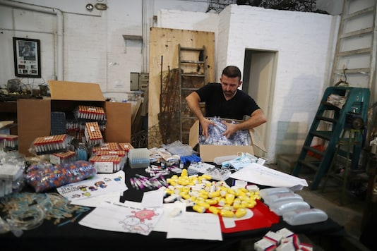"""Argentine artist Marcelo Toledo opens a box with syringes that will be part of the """"Museum of the After"""", at his workshop in Buenos Aires, Argentina.  REUTERS/Agustin Marcarian"""