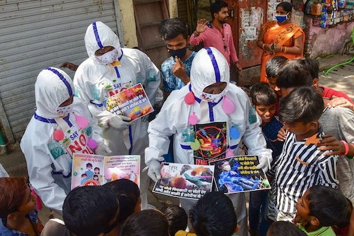 Social workers  distribute pamphlets among residents of Dharavi slums during an awareness campaign on not to celebrate Holi this year. (PTI)