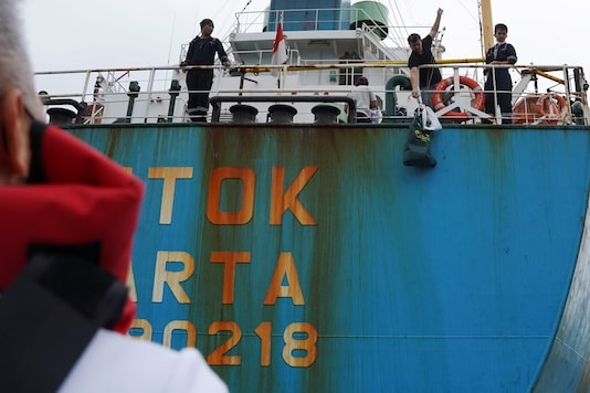 A sailor on an Indonesia-flagged cement carrier pulls a bag as the Mission of Seafarers delivers supplies to sailors stranded on visiting cargo vessels.  REUTERS/Lam Yik