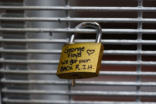 A lock bearing George Floyd's name is seen fastened to the fencing outside Hennepin County Government Center after the first day in the trial of former police officer Derek Chauvin, who is facing murder charges in the death of George Floyd, in Minneapolis, Minnesota, U.S., March 29, 2021. REUTERS/Nicholas Pfosi
