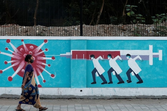 A woman wearing a protective face mask walks past a graffiti, amidst the spread of the coronavirus disease (COVID-19), on a street in Mumbai, India, March 30, 2021. REUTERS/Francis Mascarenhas