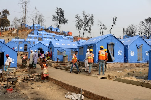 Volunteers from aid agencies rebuild shelters for Rohingya refugees who lost their dwellings to a devastating fire at Balukhali camp at Ukhiya in Cox's Bazar district, Bangladesh, Wednesday, March 24, 2021. (AP Photo)